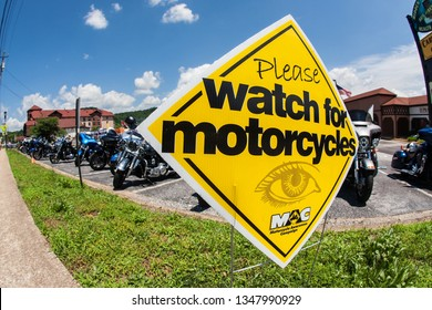 Helen, GA / USA - June 2 2018:  A sign warning people to watch for motorcycles, sits in front of a row of motorcycles parked in a parking lot at an event on June 2, 2018 in Helen, GA.