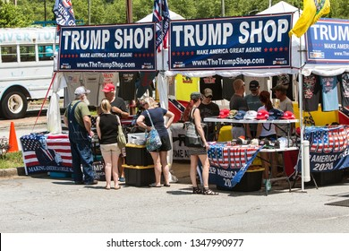 Helen, GA / USA - June 2 2018:  People look over the merchandise at the Trump Shop, a popup outdoor store selling Donald Trump apparel and other items in a parking lot on June 2, 2018 in Helen, GA.