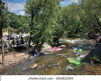 Helen, Georgia/ USA-October 8,2018 : Tourists enjoy with tubing in Chattahoochee river passing German restaurant  in Alpine Helen, GA.