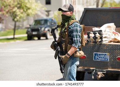 Helena, Montana - May 20, 2020: An armed man, militia member, protest at the Capitol building, holding a semi-automatic weapon in a street at the capitol, member of The Continentals with a gun.