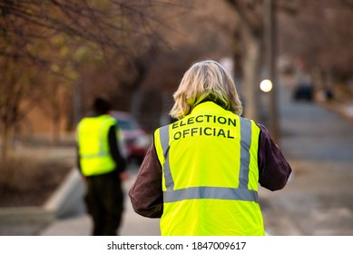Helena, Montana / November 3, 2020: Gray haired woman election official from behind, helping voters at polling station, yellow vest, presidential primary Election Day voting, people in street.