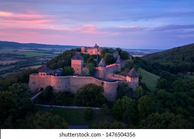 Helfstyn castle (German: Helfenstein, Helfstein), aerial view of a medieval gothic castle on a knoll over countryside. Castle walls in vibrant colors of setting sun. Czech landscape, Moravia region.
