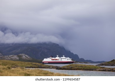 Helgeland, Norway, Europe - summer 2018: Hurtigruten coastal vessel Polarlys passing Syv Sostre mountain range in Helgeland archipelago on cloudy day.
