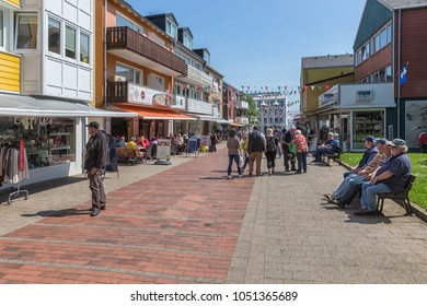 HELGOLAND, GERMANY - MAY 22, 2017: Shopping people in main street of Helgoland with many billboards. Day trippers come to the island to do tax-free shopping, Some people are resting at a bench.