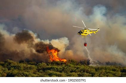 Hubschrauber mit Bambi-Eimer, der Wasser über die Flammen wirft