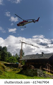 helicopter carries cargo in the Alps at a construction site