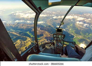 Helicopter cockpit flying on mountain landscape and cloudy sky, with pilot arm driving in cabin. Spectacular aerial view of Alps.
