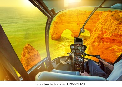 Helicopter cockpit interior flying on natural arches of Praia da Marinha in Algarve, Portugal, Europe. Scenic flight above Marinha Beach. Famous place for summer holidays in Portugal.