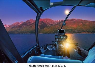 Helicopter cockpit interior flying on Jackson lake Wyoming. Scenic flight above Jackson lake skyline. Night urban aerial scene.