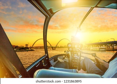 Helicopter cockpit interior flying on Quay Bridge on Swan River in Elizabeth Quay marina at sunset. Scenic flight above Perth, Western Australia skyline. Urban aerial scene with copy space.