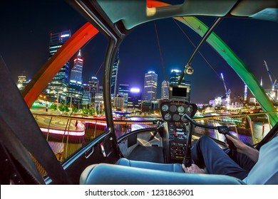 Helicopter cockpit interior flying on Elizabeth Quay Bridge by night on Swan River at entrance of Elizabeth Quay marina. Scenic flight above Perth, Western Australia skyline. Night urban aerial scene.