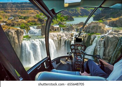 Helicopter cockpit with pilot arm and control console inside the cabin in aerial view flight on Shoshone Falls or Niagara of the West, Snake River, Idaho, United States.