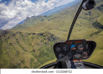 Helicopter cockpit view flying over mountains