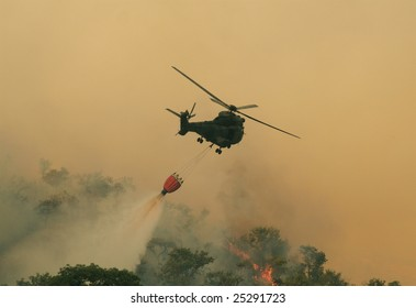Helicopter dousing flames of bush fire