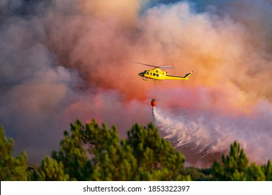 Hubschrauber, die Wasser mit Bambi-Eimer über das Feuer werfen