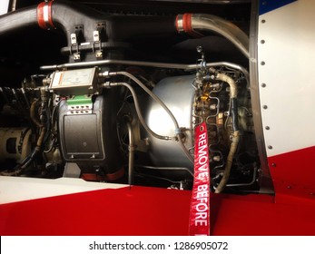 Helicopter engine with cowling off and 'remove before flight' red tag. The engine of the helicopter has been opened with cowling off during the heavy maintenance