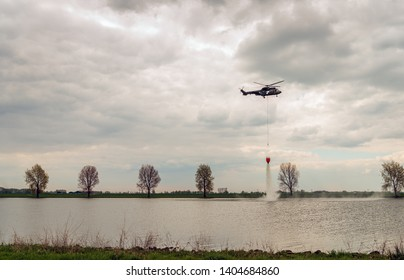 Helicopter exercises with a specialized bucket suspended on a cable to deliver water for aerial firefighting. The photo was taken at the Dutch river Bergsche Maas near Dussen, North Brabant.