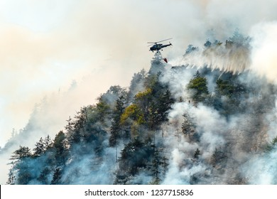 helicopter extinguishes forest fire on the slope of a fuming mountain