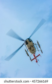 helicopter flying above with propeller blades blurred by fast motion.