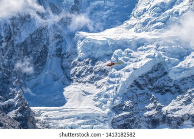 Helicopter flying between snow mountains for rescue