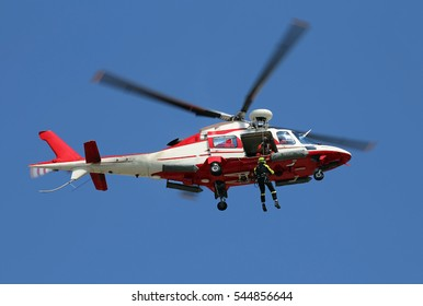 Helicopter flying firemen while a fireman descends from above with the winch