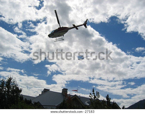 Helicopter flying low overhead  on a summer day, in Whistler BC, Canada