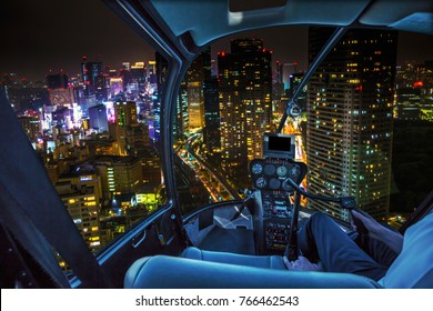 Helicopter flying over Tokyo cityscape and Shiodome skyscrapers and business offices view from skyline at night, Tokyo, Japan.