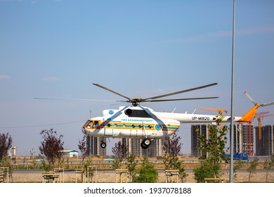 A helicopter flying in the sky over Kazakhstan. Helicopter mass media TZhK against the background of the construction site of the city of Turkestan. Kazakhstan, Turkestan - 14 March 2021
