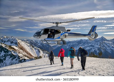 The helicopter hovered over the mountain mama. 4 people escape and climb aboard a helicopter.