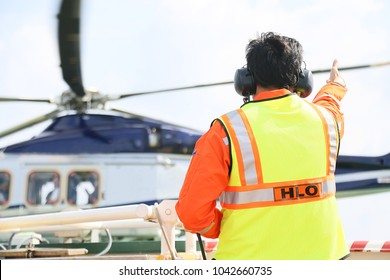 Helicopter Landing Officer communicating  with pilot and copilot for service on ground and support as the pilot required. The helicopter landing on the deck in oil and gas platform