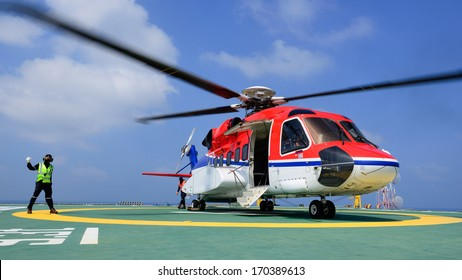 The helicopter landing officer give signal to passenger to embark helicopter at oil rig platform