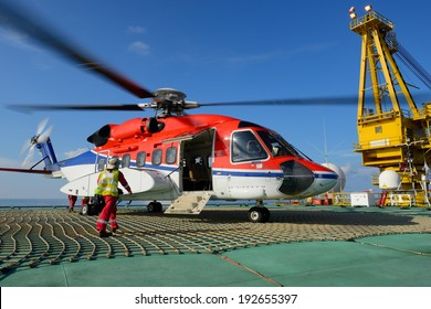 The helicopter landing officer is going to helicopter at oil rig platform