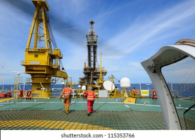The helicopter landing officer are walking back after take care passenger to embark helicopter at oil rig platform is in the gulf of Thailand.