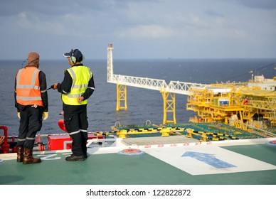 The helicopter landing officers are on the oil rig.