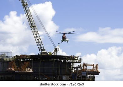 Helicopter landing on offshore oil rig.