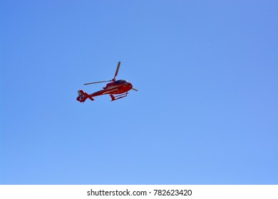 Helicopter, mid flight with clear blue sky as a background, isolated.