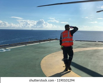 Helicopter officer on offshore helipad beside helicopter or The helicopter landing officer is on the oil rig platform in the gulf of Thailand.