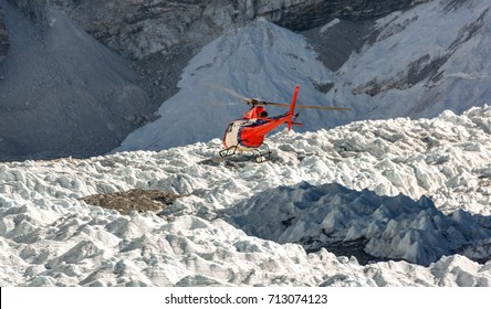 The helicopter on the background of the Khumbu glacier near Everest Base Camp - Everest region, Nepal, Homalayas