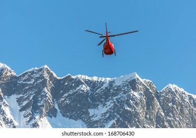 Helicopter on background of the Mahalangur Himal ridge - Everest region,