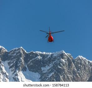 Helicopter on background of the Nuptse massif - Everest region, Nepal, Himalayas