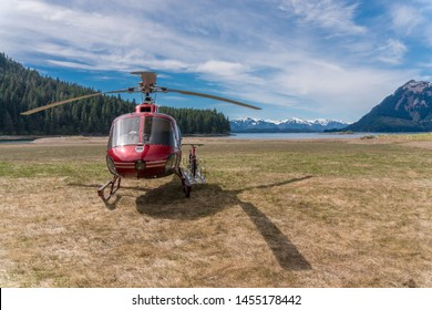Helicopter on the beach in Alaska. This is excursion to the mountains by chopper and after by bicycle. Beautiful nature, beach behind the aircraft. Glacier expedition and exploration.
