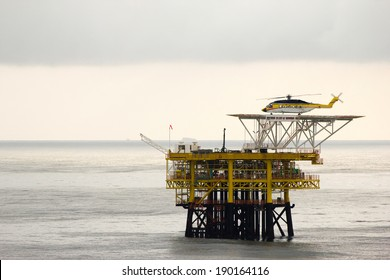 A helicopter on top of a offshore oil-platform transporting roughnecks to nearby rigs