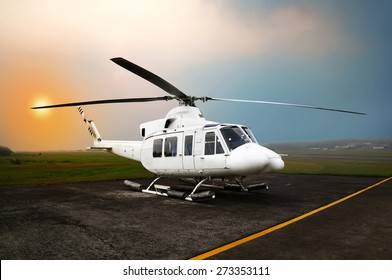 Helicopter parking on the airport. With sunset sky background