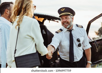 Helicopter pilot shaking hands with woman and smiling. Couple traveling through a private helicopter with pilot greeting them.