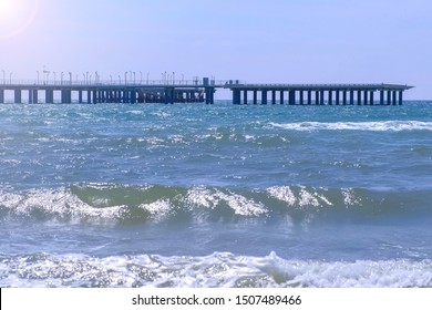 Helicopter platform and big pier at sea and stormy sea waves at windy day. Beautiful sea ocean background. Nature seascape with long waves, sky and pier at sunny day.