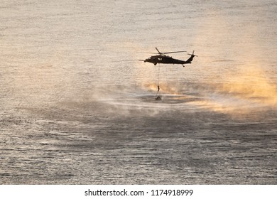 Helicopter in plumes of water vapor and drizzle at sunset. Mock up rescue mission above the Columbia river. Navy person descends down the rope.
