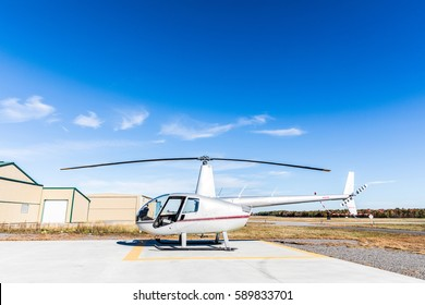 Helicopter side view at heliport on a sunny day. Small helicopter with hangar and runway on background. Transport and travel concepts