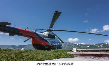 The helicopter is standing on a green meadow in the caldera of an extinct volcano. A picturesque mountain range against the blue sky. In the foreground are the steps of a wooden staircase. Kamchatka
