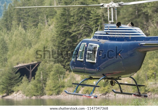 A Helicopter taking off near Three valley gap at Revelstoke British Columbia Canada