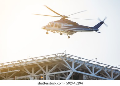 Helicopter transferring oil rig worker between shore and offshore, Chopper landing on heli deck at platform accommodation area.